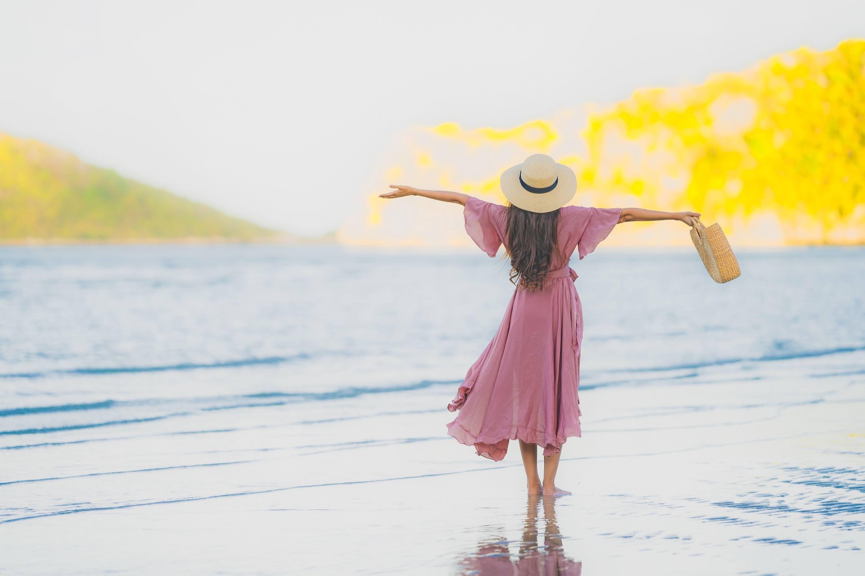 A woman enjoying standing on a beautiful beach
