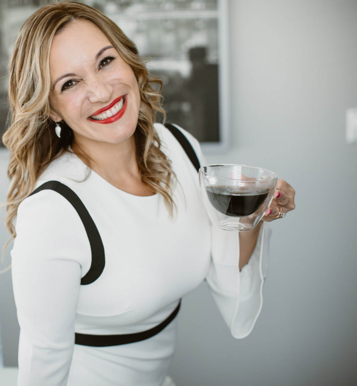 Photo of Dr. Paola smiling with a cup of coffee