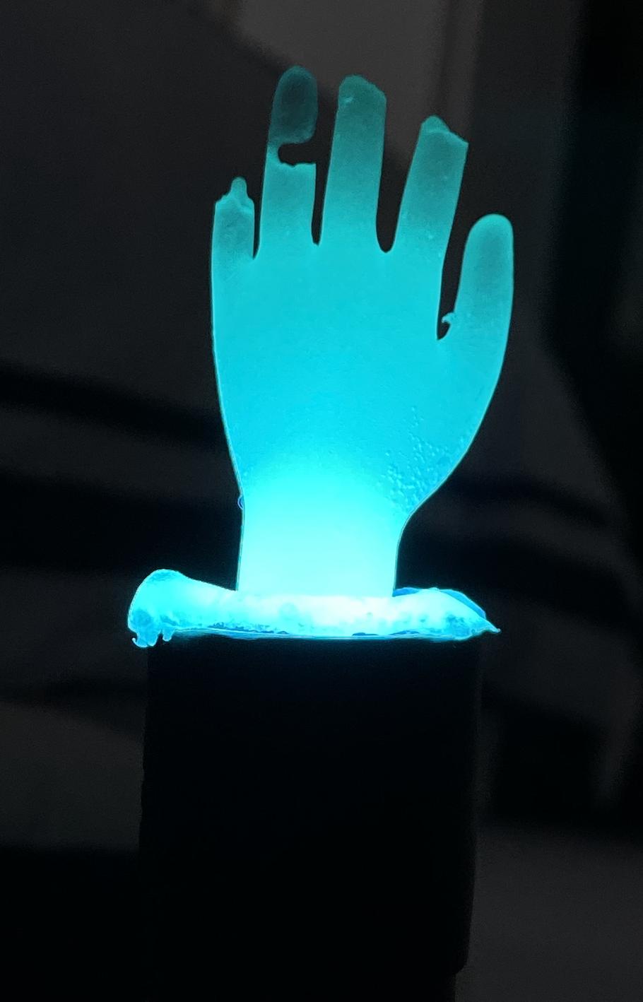 Fluorescent epoxy hand lit by UV light.
