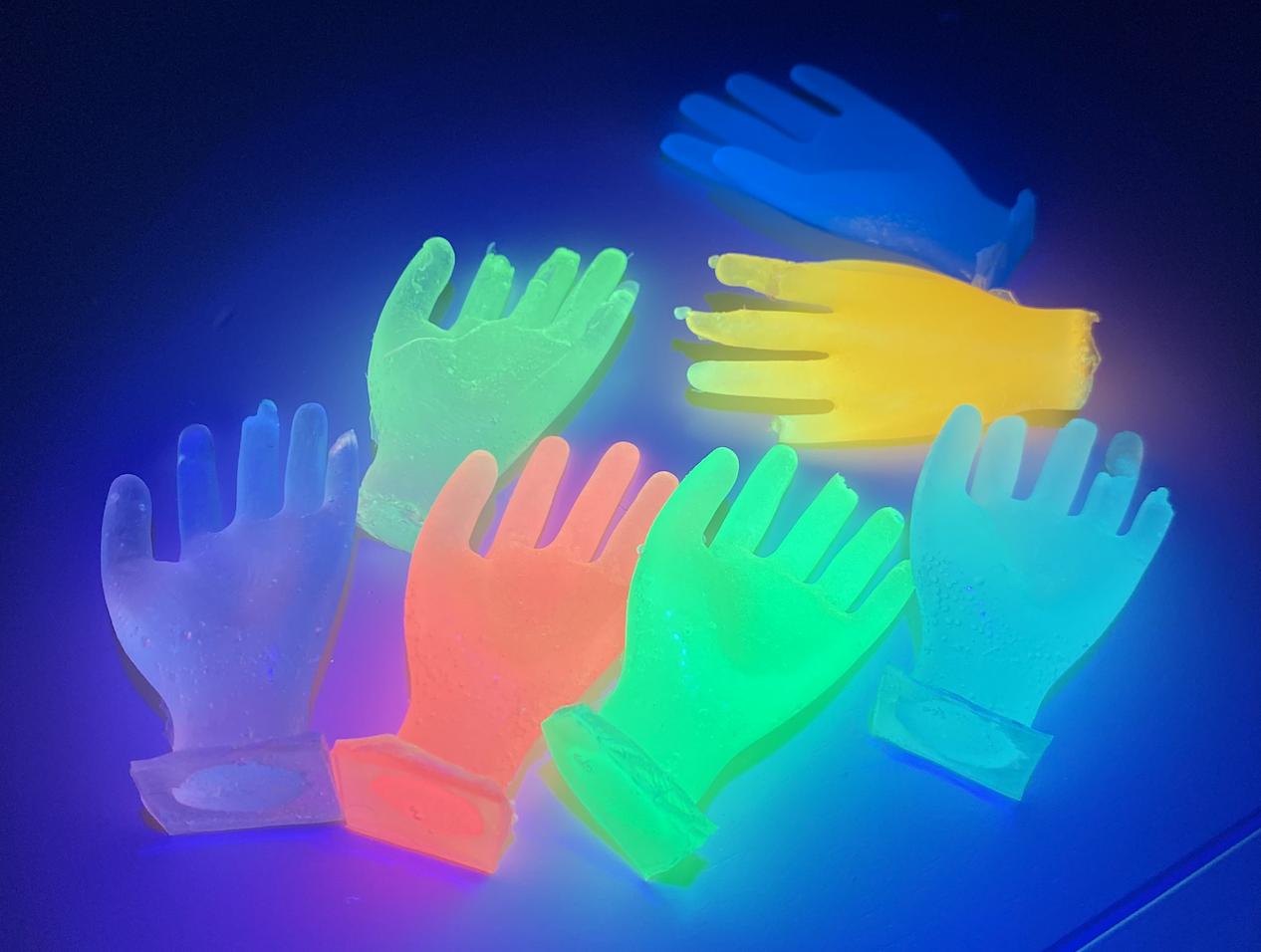 Many fluorescent epoxy hands lit by UVlight.