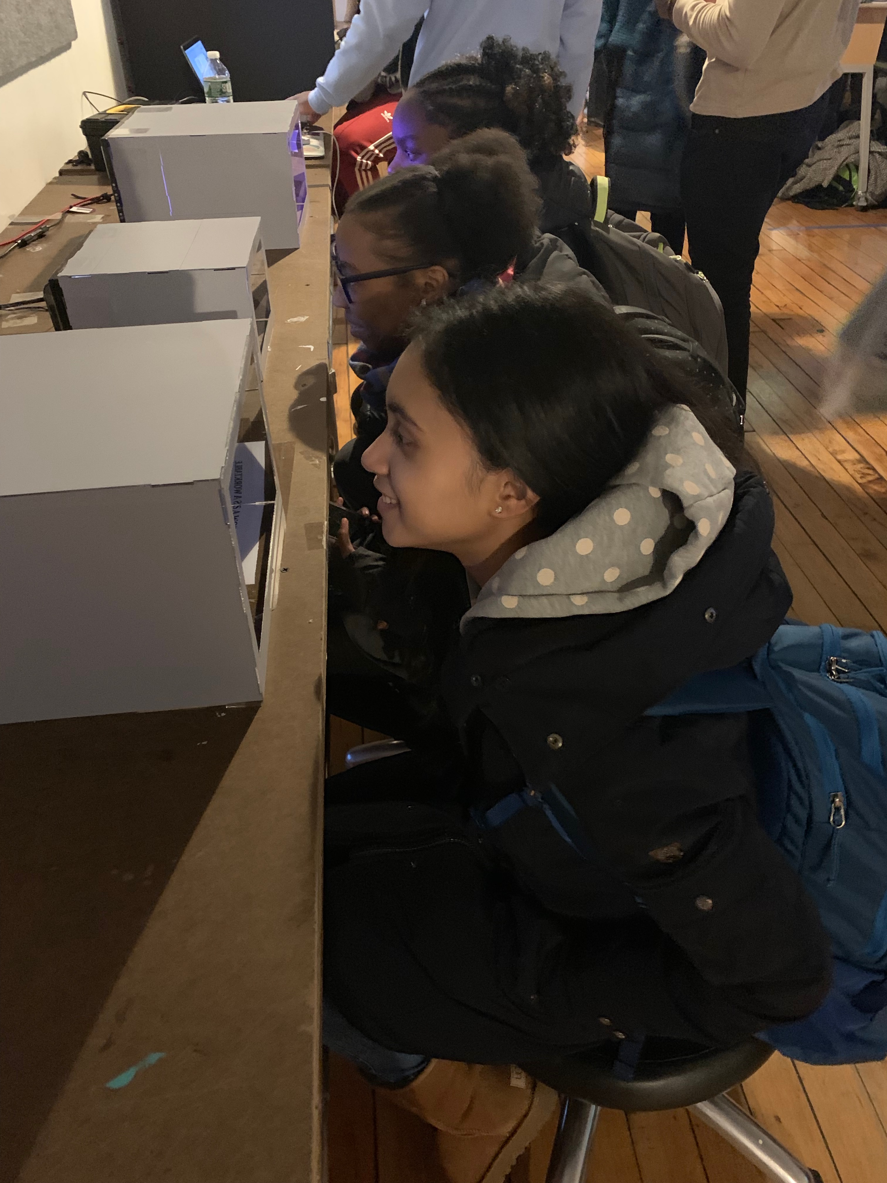 Girls looking into mirror boxes.