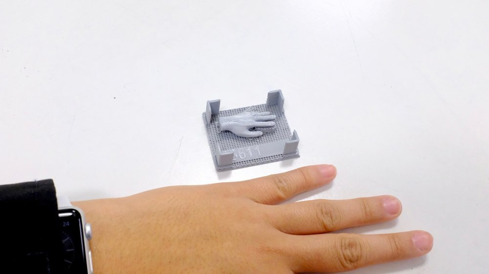 After printing, with support structure still attached, human hand for size reference