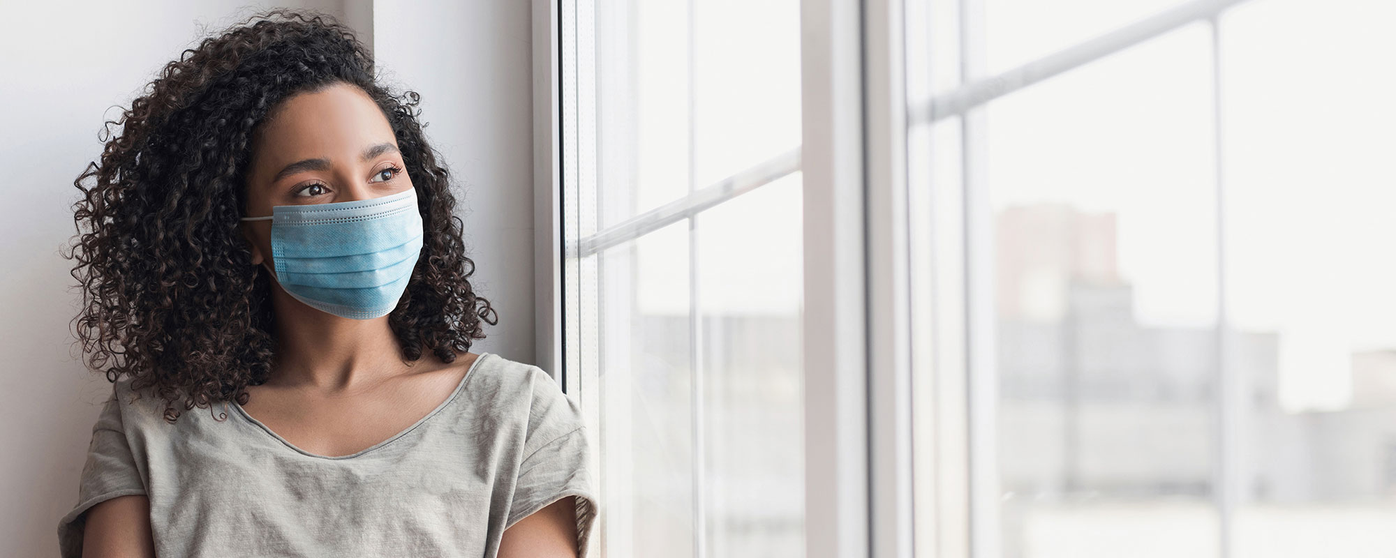 Woman wearing medical mask looking out window