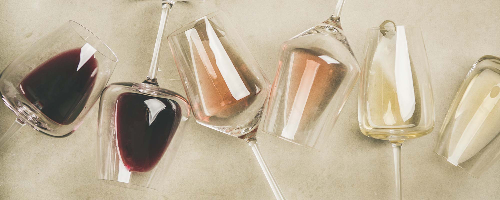 Close up, wine glasses in a row tipped over sideways on a table