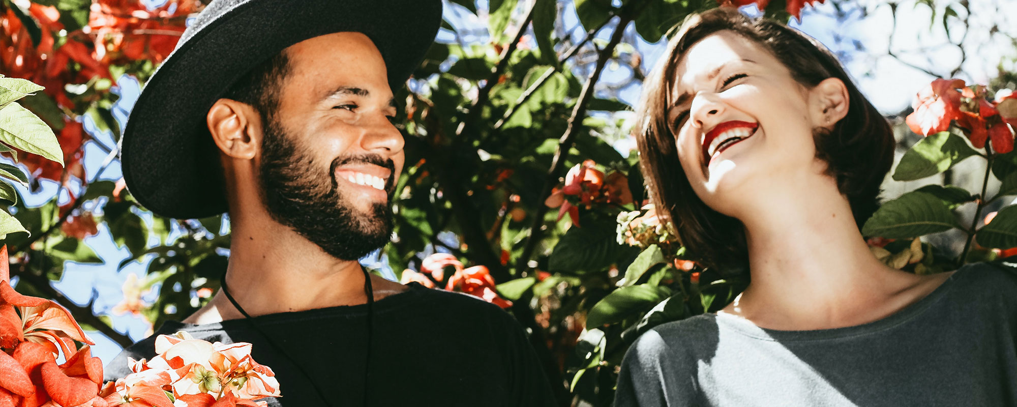 A couple on a date smiling and laughing together, surrounded by flowers in a tree