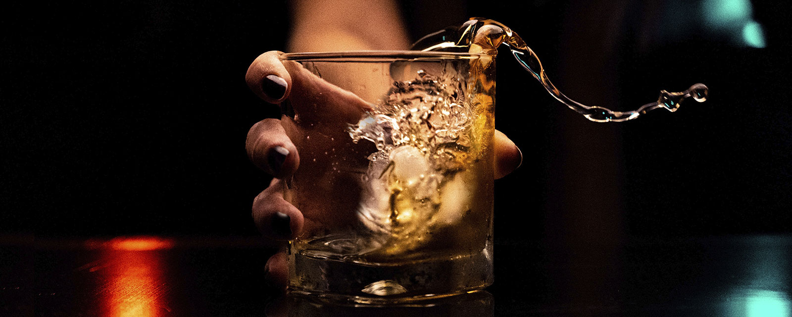 A hand holding a cocktail with the contents spilling out