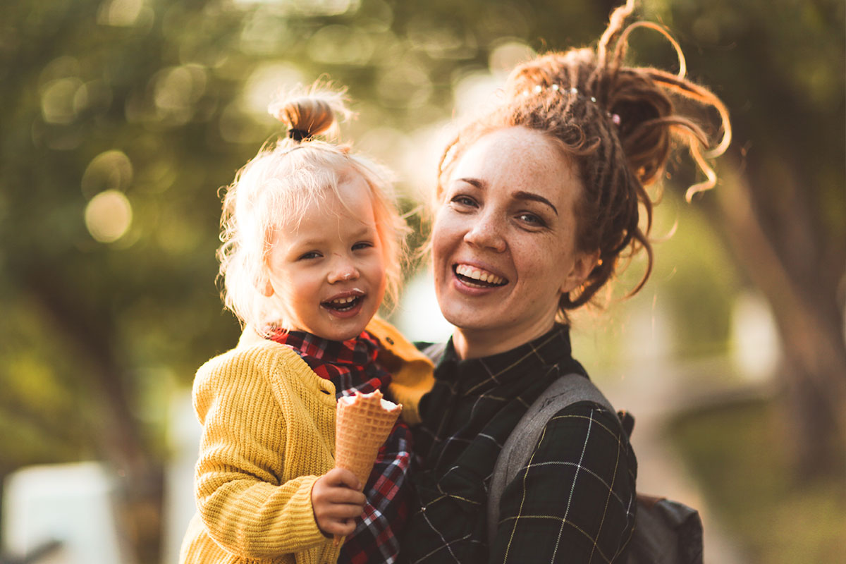 A mother holding a happy baby eating ice cream