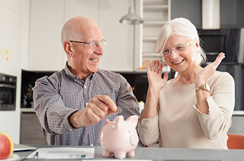 An older couple putting coins into a piggy bank.