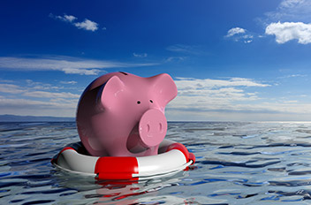 Pink piggy bank floating on a round red and white floaty in the ocean.