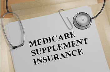 Medicare Supplement Insurance title on paper and a stethoscope.