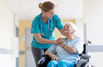 Elderly woman sitting in a wheelchair smiling at the female nurse touching her shoulder.