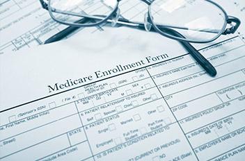 Glasses sitting on a medicare enrollment form.