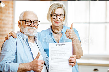 Older couple giving thumbs up to the camera, holding insurance form.