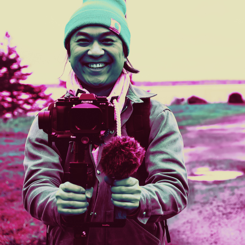 Daniel Hoang holding a camera wearing a beanie hat.