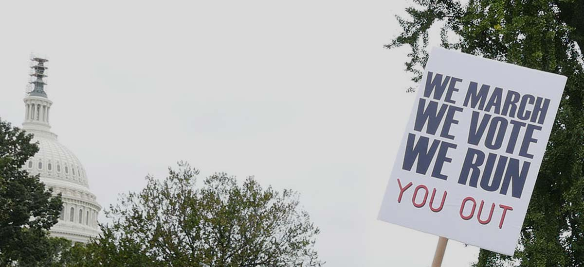 "Photo of a protester's sign saying ""We March, We Vote, We Run You Out"""