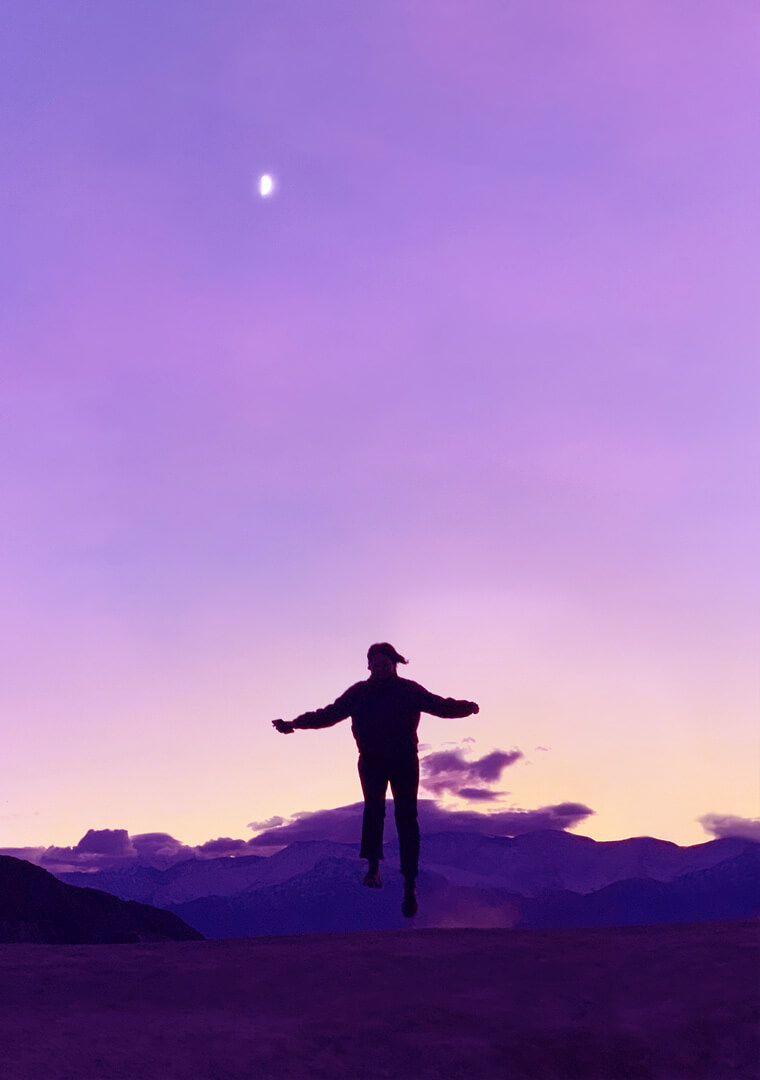 Man with arms reaching out in front of lilac sunset.
