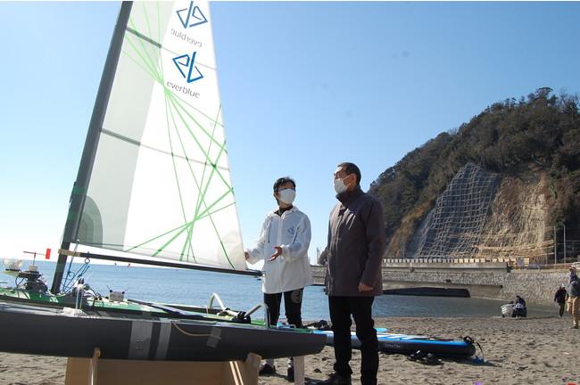 逗子海岸での海上テストに訪れた、桐ケ谷逗子市長に説明する野間代表