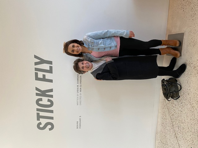 """Ann Hoenig, Co-founder of Hoenig Theatre Artist Scholarship, in a black coat is standing next to Kayla Raelle Holder, 2015 recipient,  in a denim jacket and black pants. They are both under the text """"Stick Fly""""."""