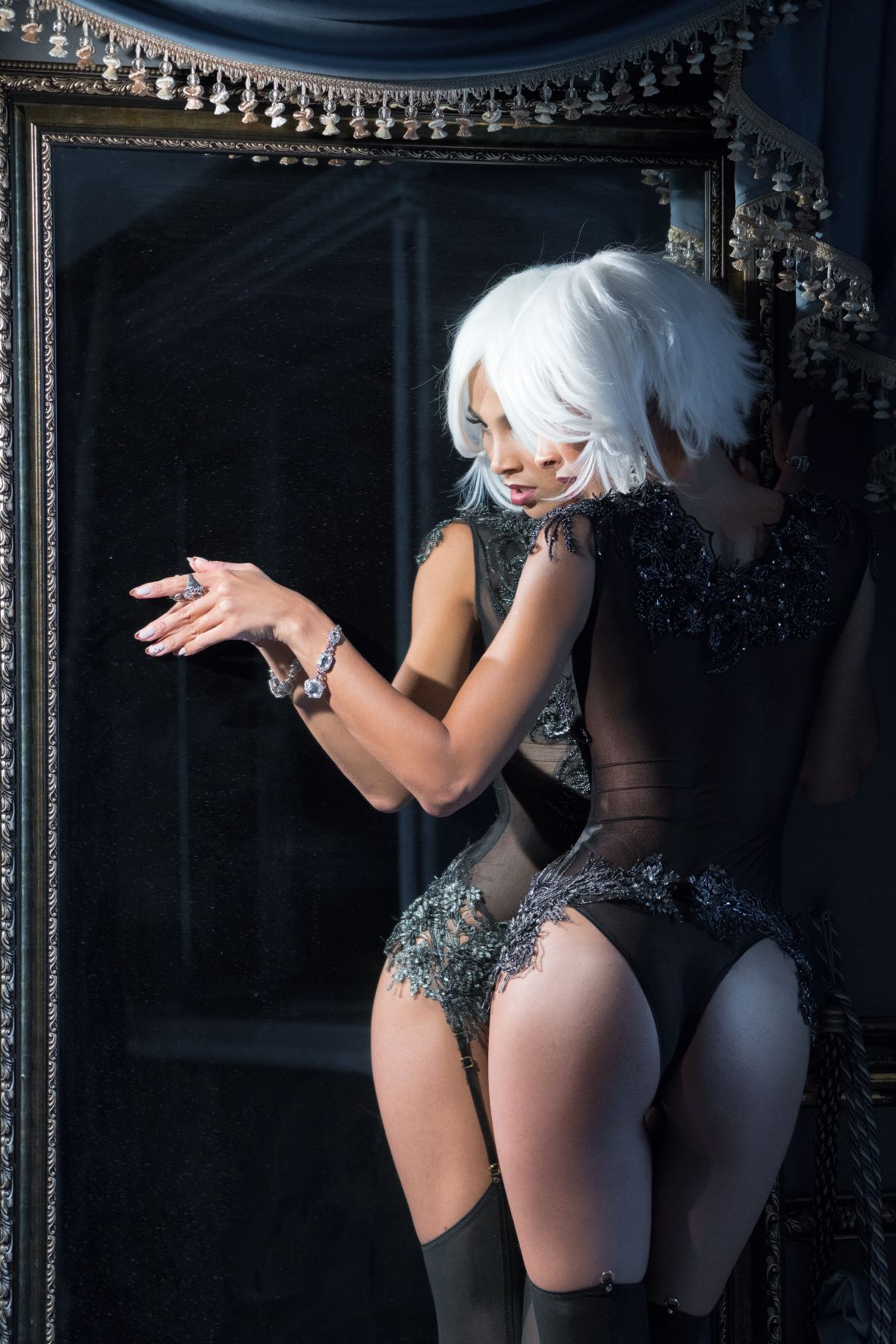 Woman in silver wig wearing lingerie and stockings in mirror