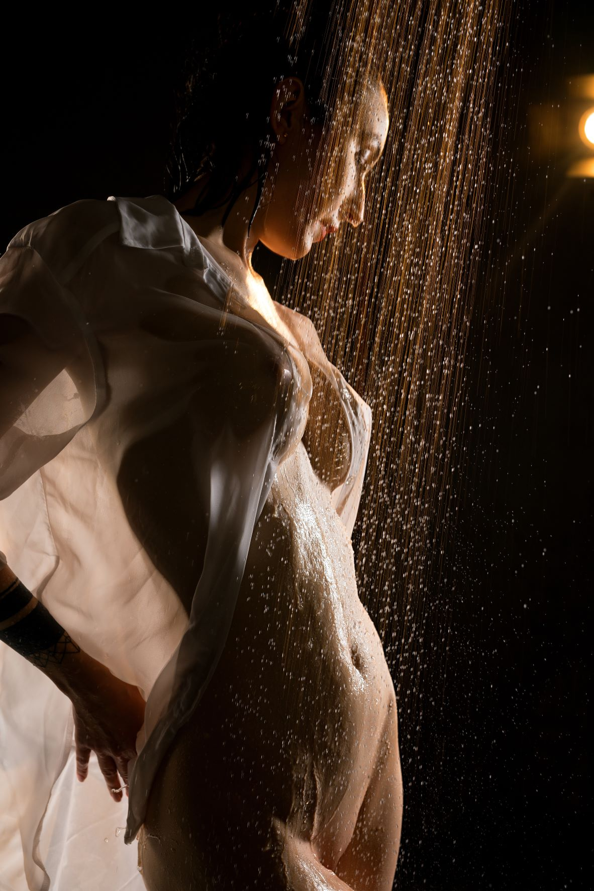 Woman in shower with wet shirt covering breasts