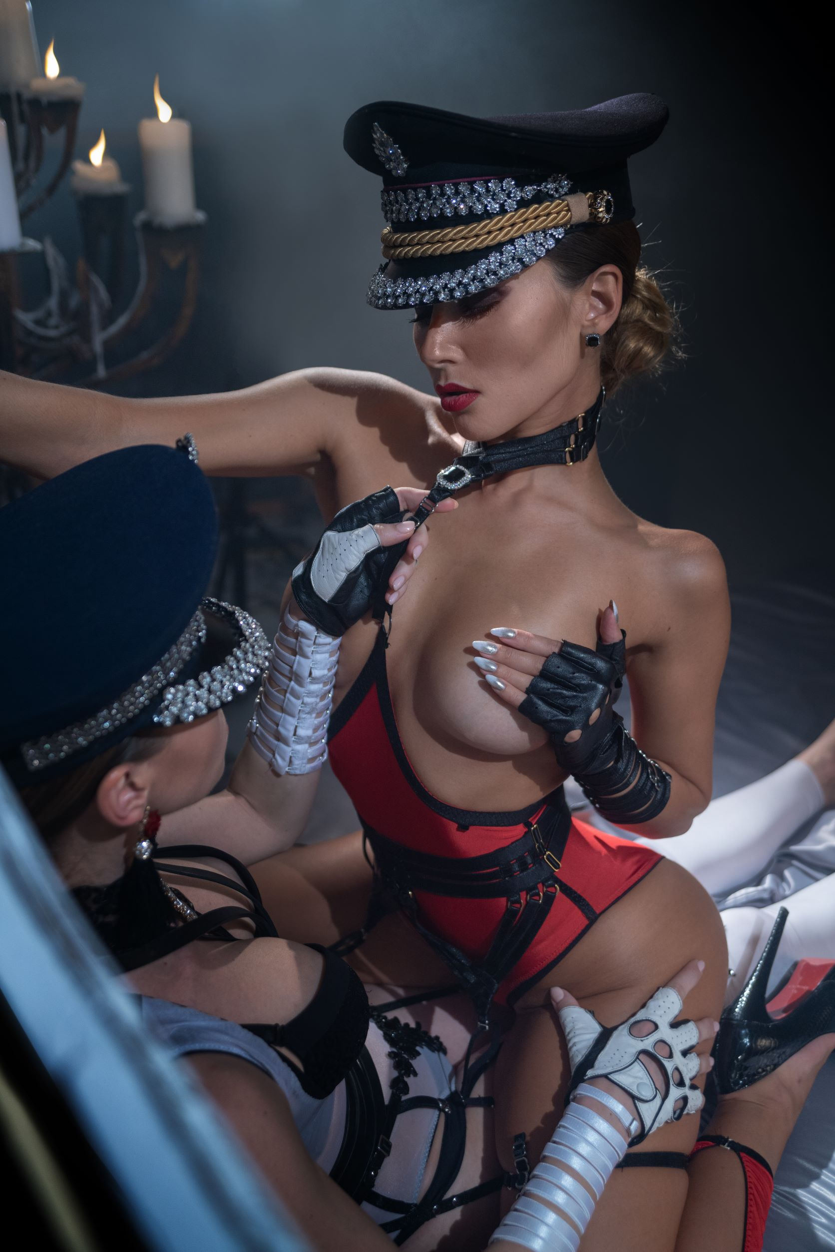Two women caressing wearing black and red lingerie and embellished hats