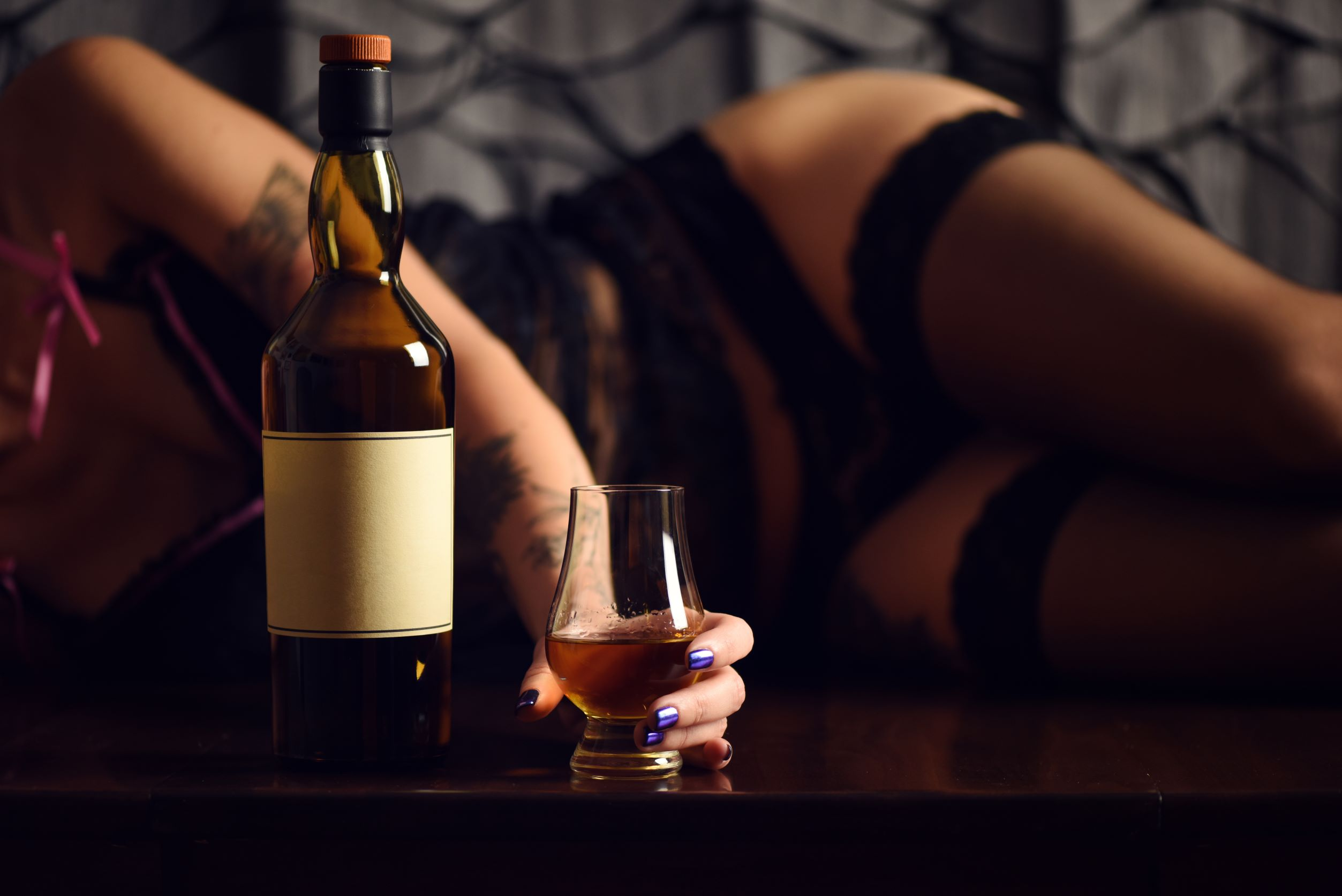 Woman laying on side in lingerie and stockings holding glass with alcohol bottle