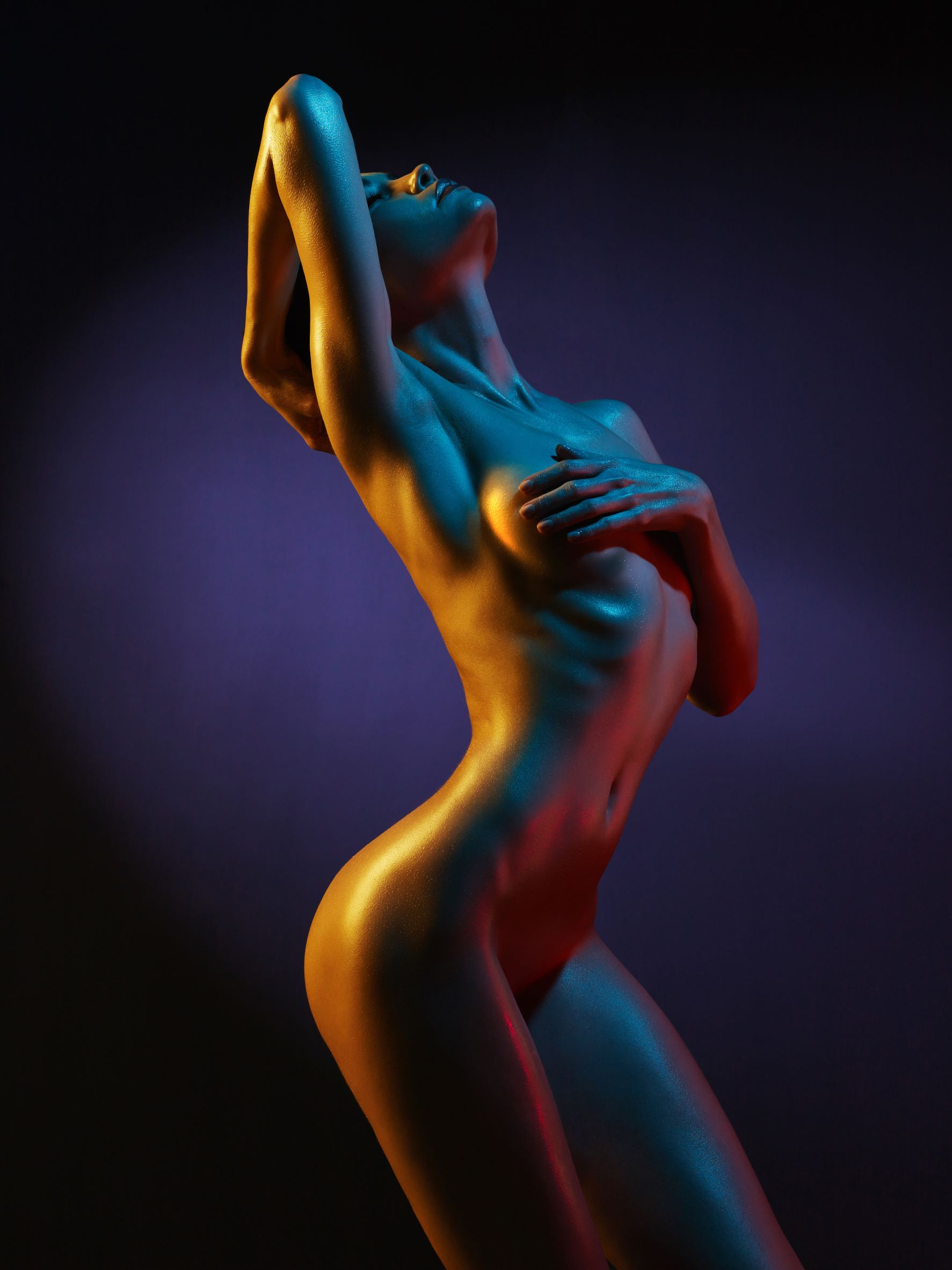 Nude woman leaning back covering breasts with hands