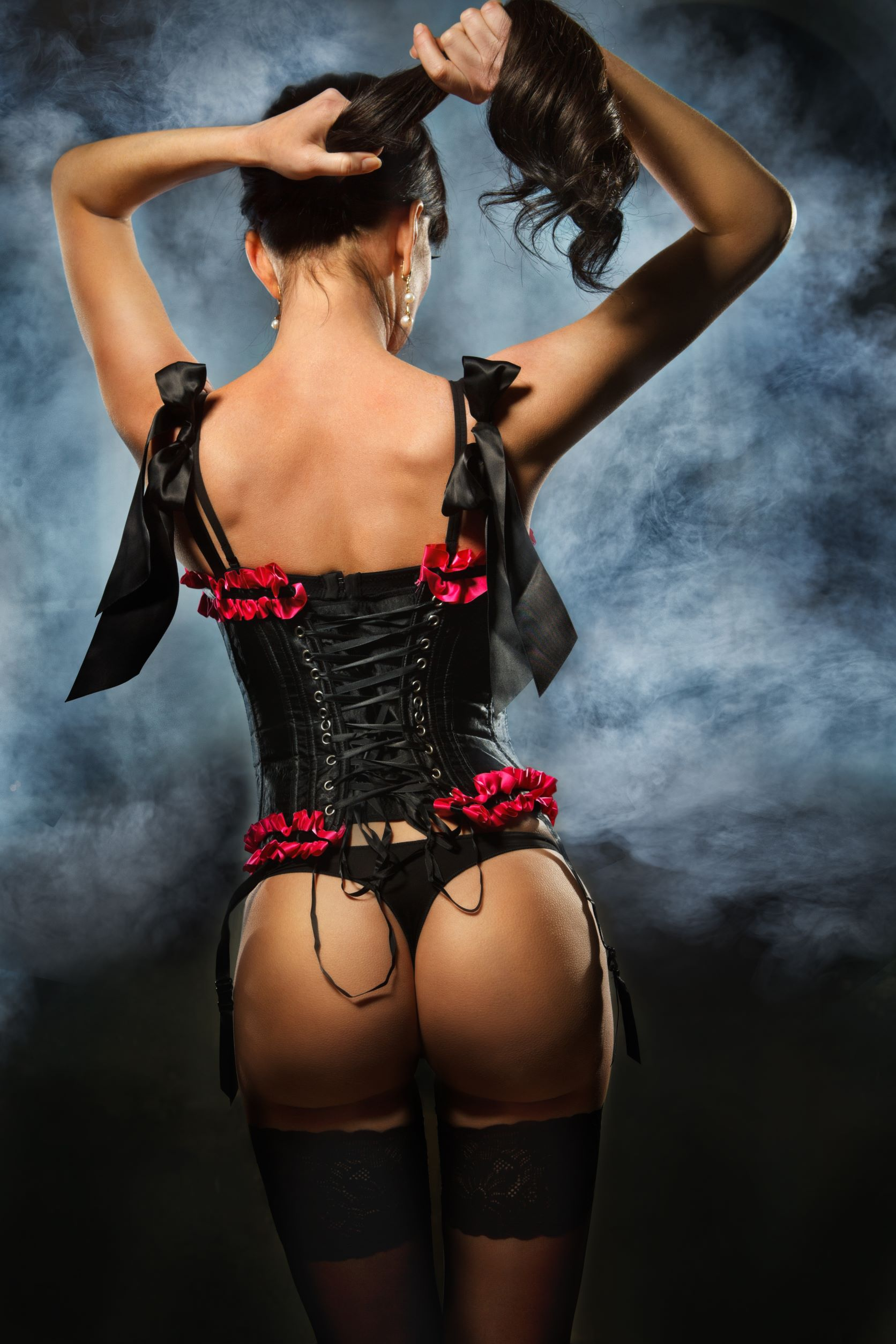 Woman in black and red lingerie with stockings and corset tying hair seductively