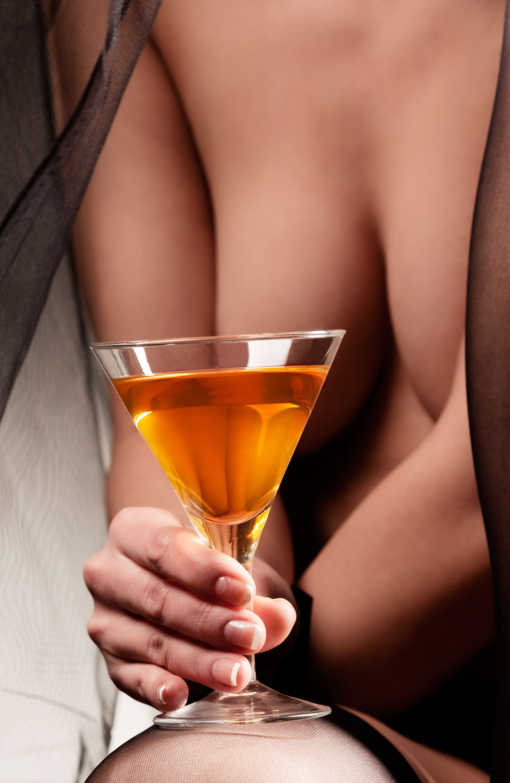 Woman covering breast with drink in cocktail glass