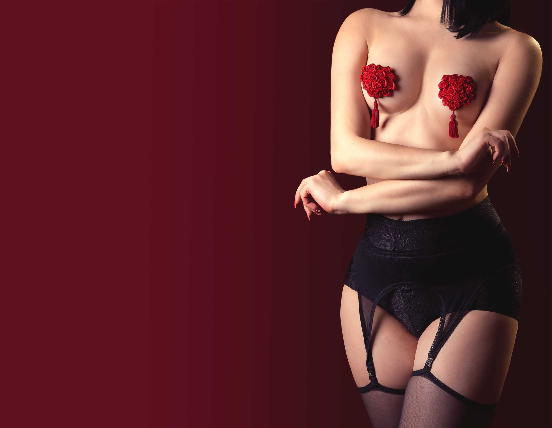 Woman wearing black panties and stockings with red rose nipple pasties