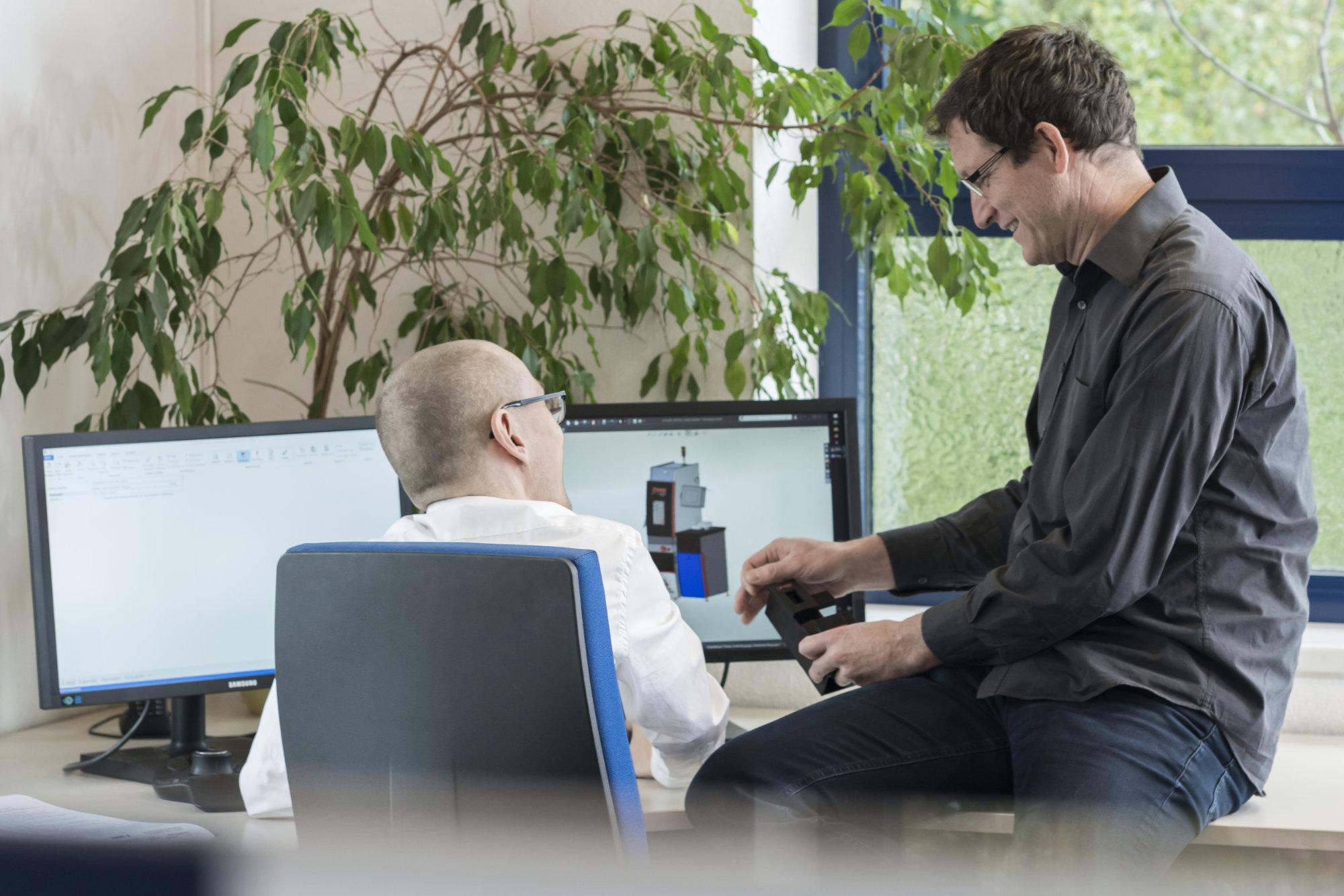 Zwei Mitarbeiter sitzen gut gelaunt vor dem Bildschirm und sprechen über ein Modell.