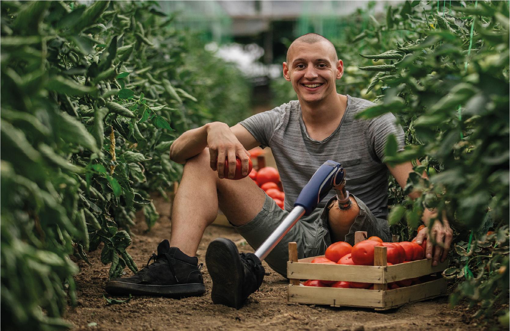 Homem alegre em meio a plantação de tomate, este pessoa possui uma perna mecânica