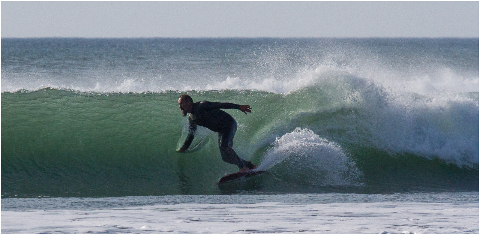 Surfer takes to the waves at Widemouth Bay near Bude in north Cornwall - one of the top 10 things to do in and around Bude