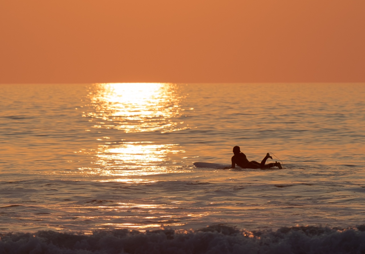 Stunning sunset photograph of a solitary surfer waiting for a wave in Widemouth Bay, north Cornwall taking by a guest staying at dog-friendly Gwelmor self-catering holiday cottage