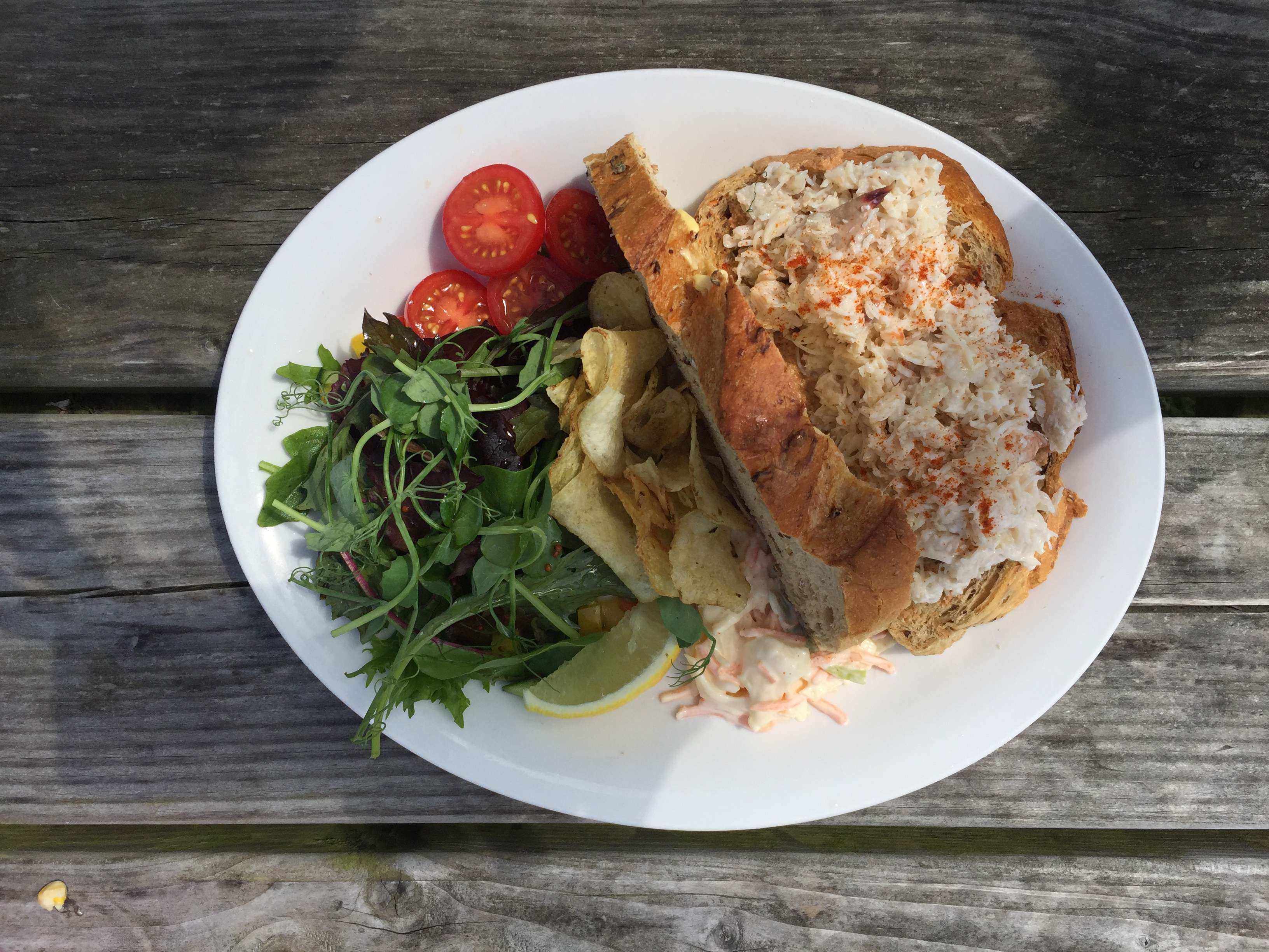 White plate with an open crab sandwich and salad
