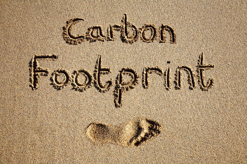Words Carbon Footprint written in the sand over the top of a footprint