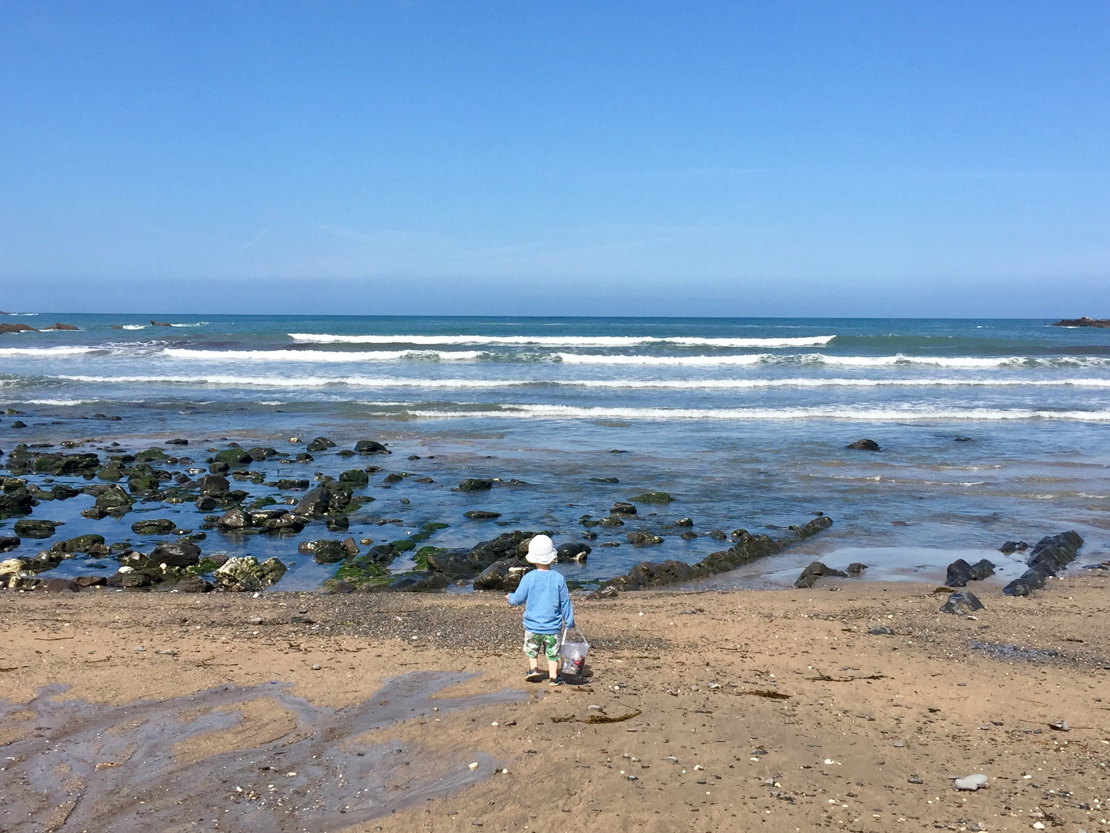 Small boy enjoys watching the waves on the beach at Widemouth Bay north Cornwall whilst staying at child-friendly Gwelmor holiday cottage