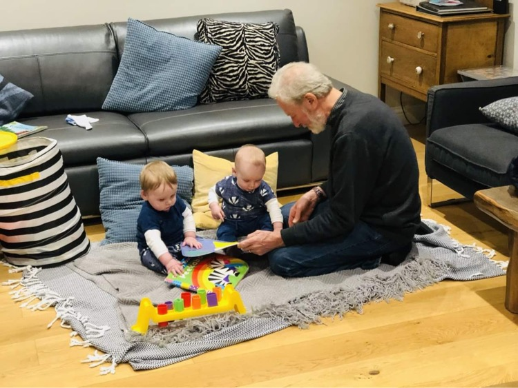 Granddad sits and plays with twin toddlers at child-friendly self catering holiday cottage Gwelmor in Widemouth Bay, north Cornwall