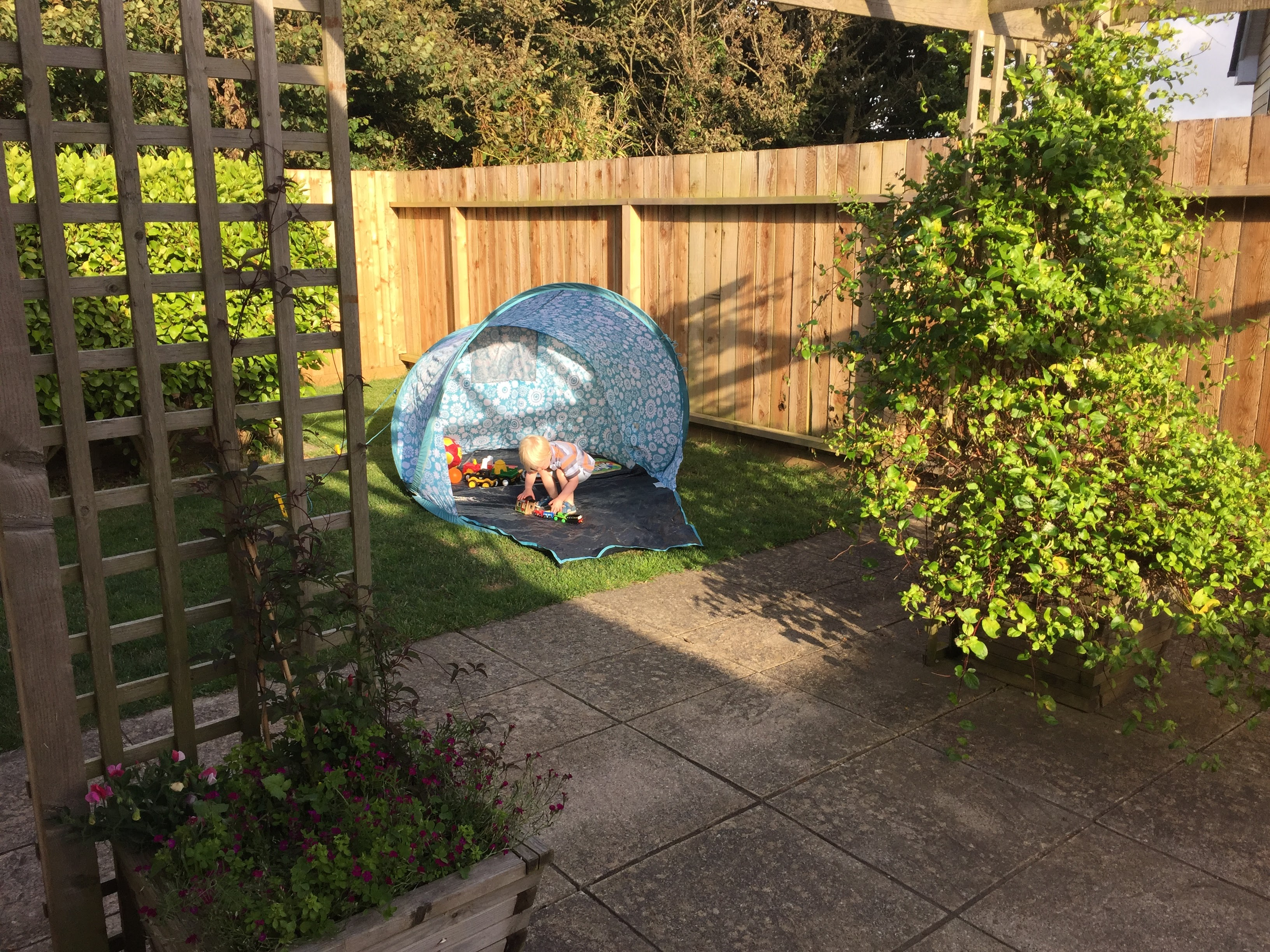 Young boy plays by himself in the fully enclosed garden at Gwelmor, in Widemouth Bay