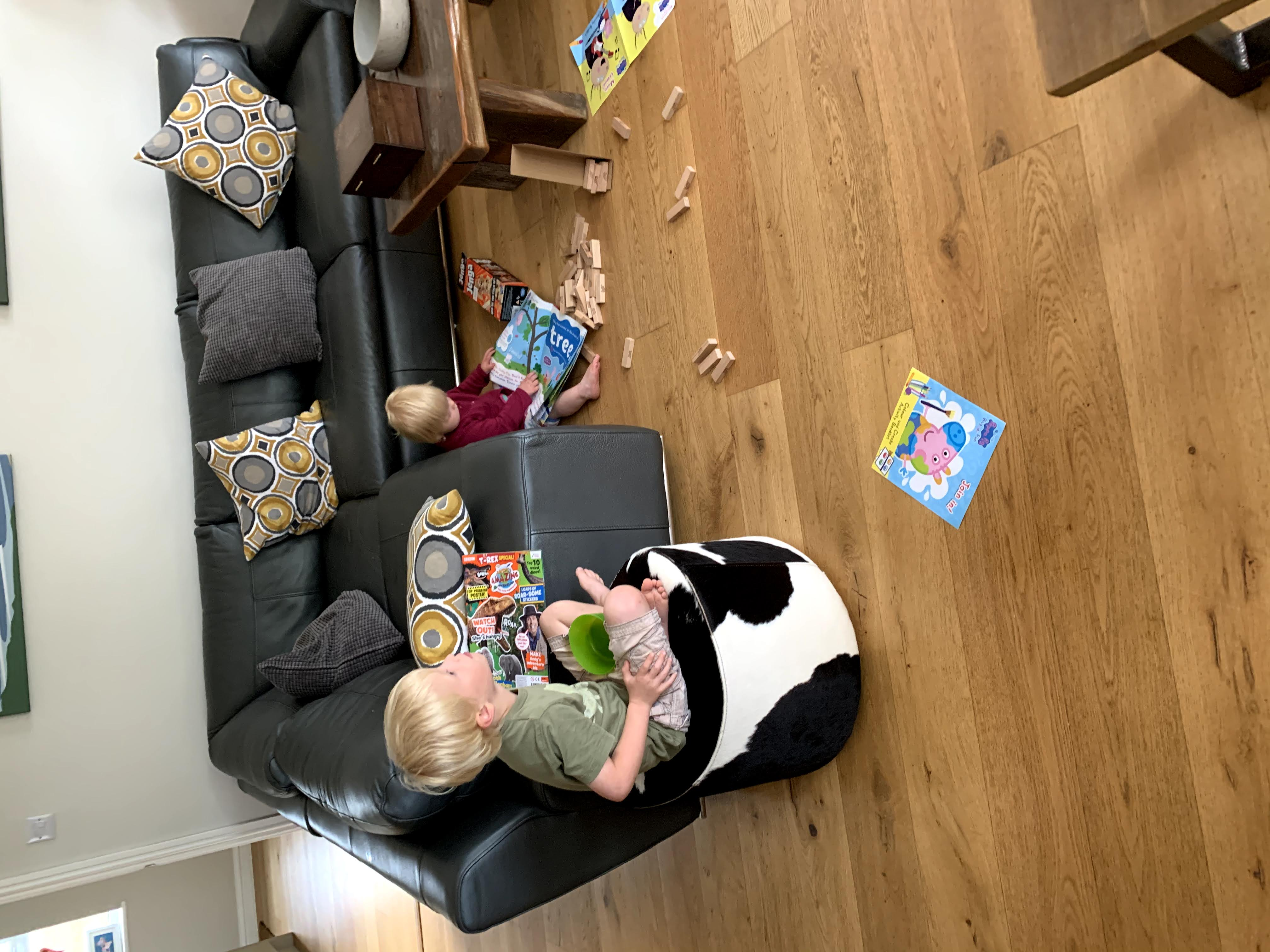 Child sits on poof whilst watching television while younger sibling plays on the floor in spacious Gwelmor, a child-friendly self-catering holiday cottage in north Cornwall