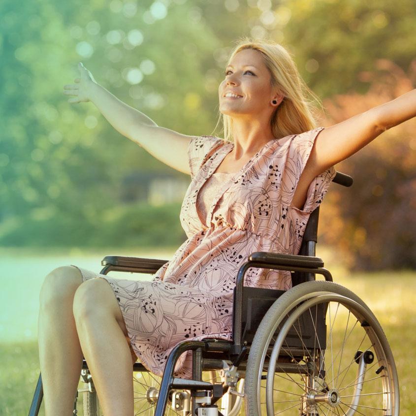 Imagem de uma mulher cadeirante sorrindo com os braços abertos num parque sentindo a luz do sol.