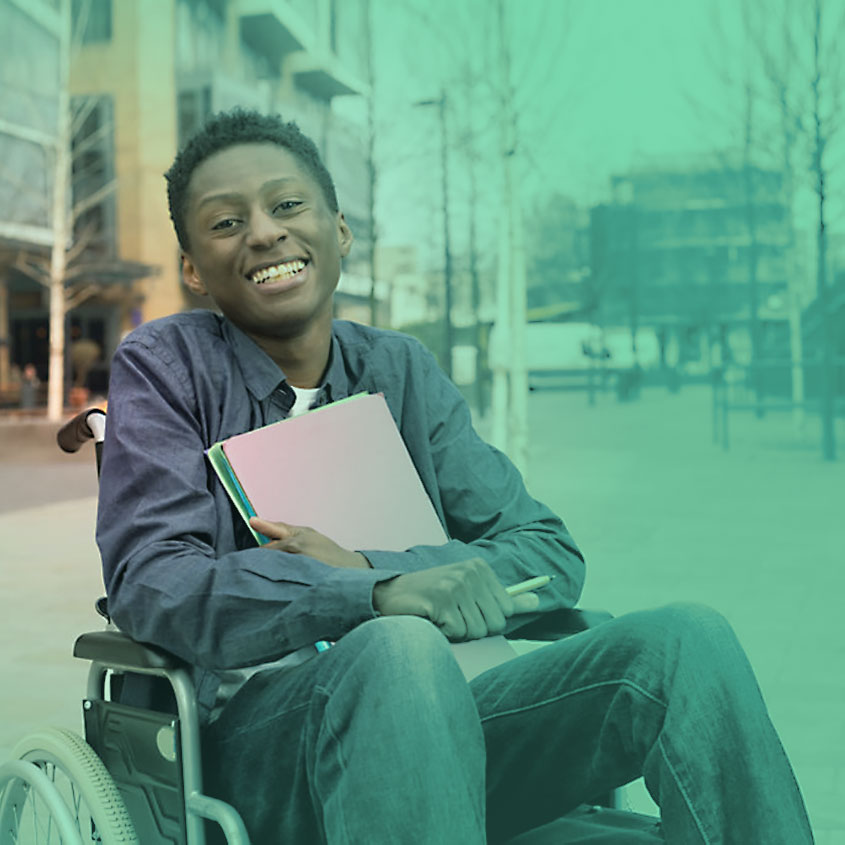 Imagem de um garoto cadeirante sorrindo no pário de uma faculdade com caderno nas mãos