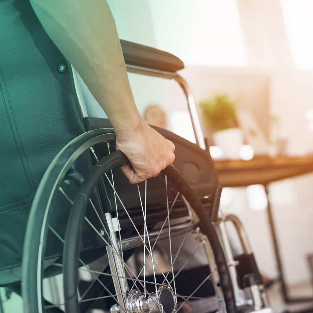 Imagem de um close das mãos de um cadeirante segurando a roda