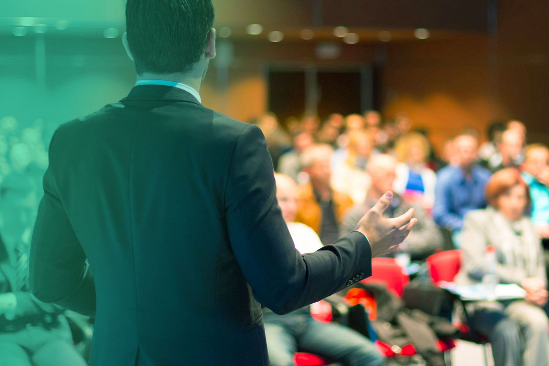 Imagem de um palestrante em frente sua platéia