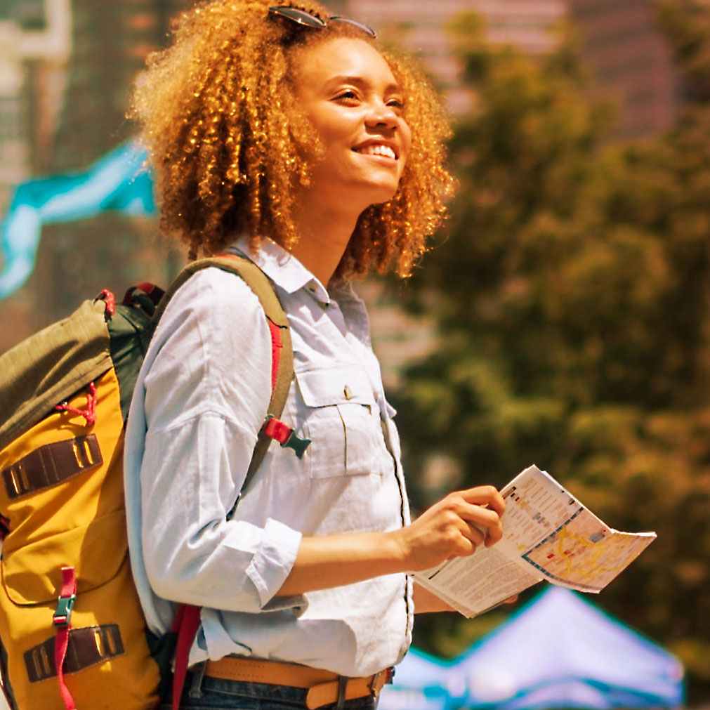 Imagem de uma mulher andando com um mapa na mão.