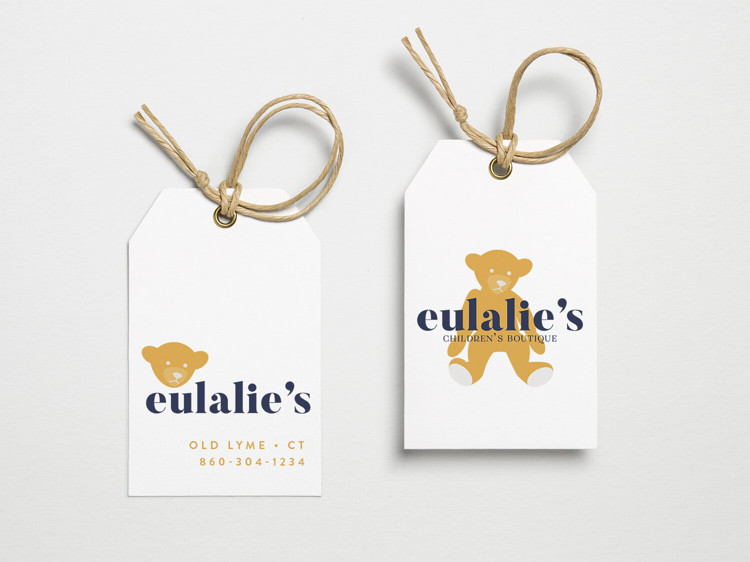 Two hang tags on a white background for a children's clothing boutique with a teddy bear logo.