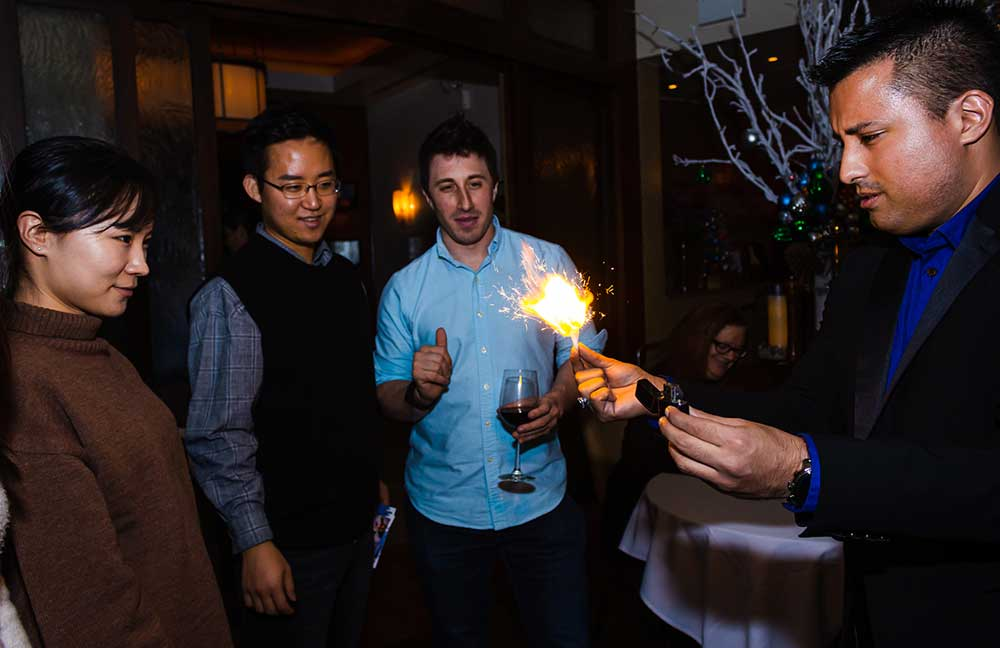 Three guests watch a paper lit on fire by a magician