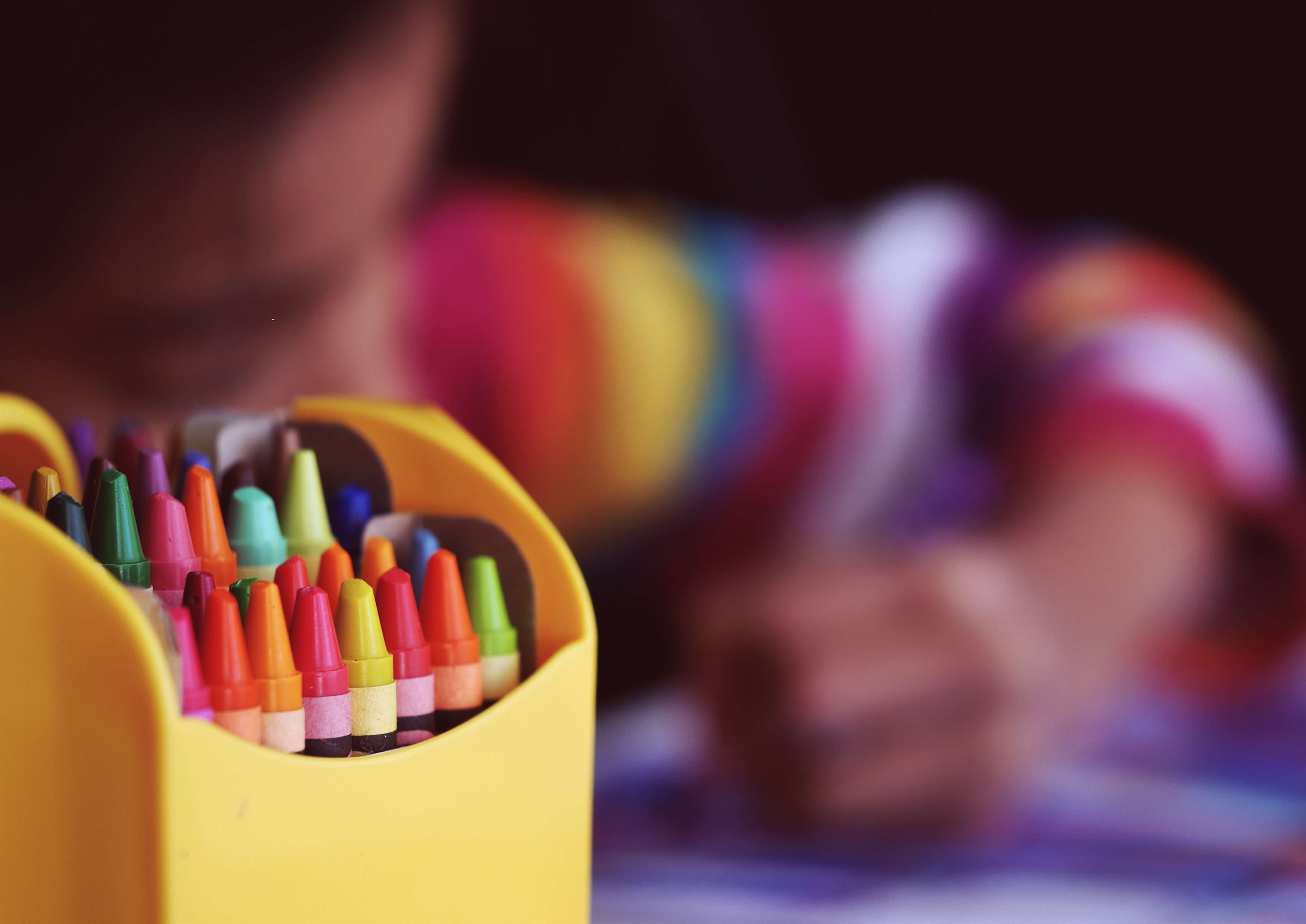child using crayons to draw
