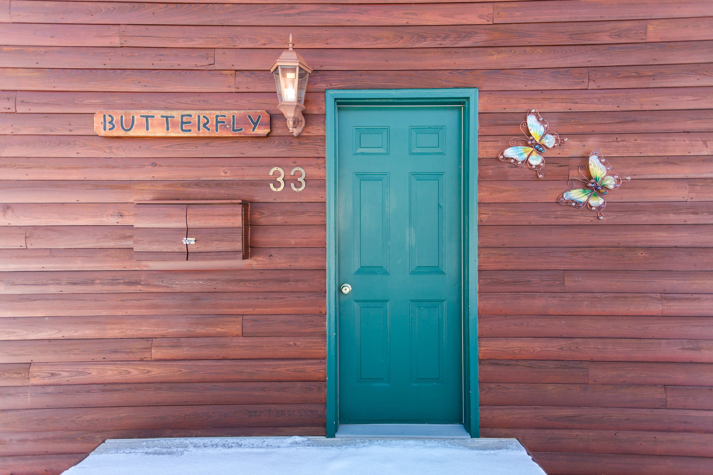 A green door of a cabin with the Name butterfly and Number 33 beside it