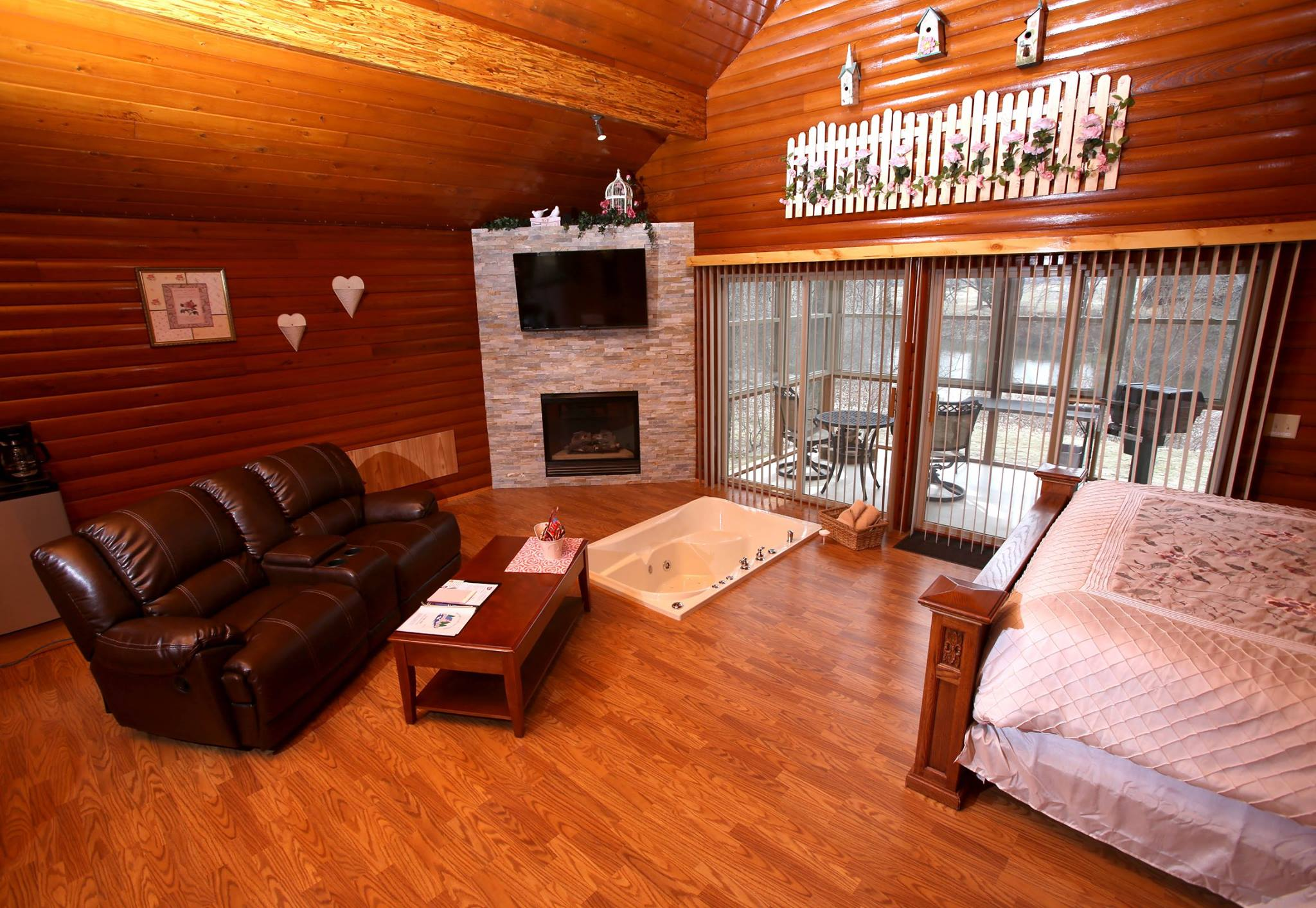 Inside of cabin showing king sized bed, gas fireplace, sunken tub and living area.